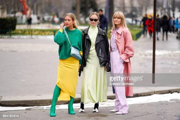 Guest wears a green sweater, a blue crossbody bag, a yellow assymmetric skirt, green over-knee boots ; a guest wears sunglasses, a black moto jacket,...