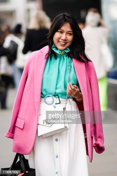 A guest wears a green top a pink jacket a white skirt with a blue round buckle and blue buttons a white Prada bag during London Fashion Week February...