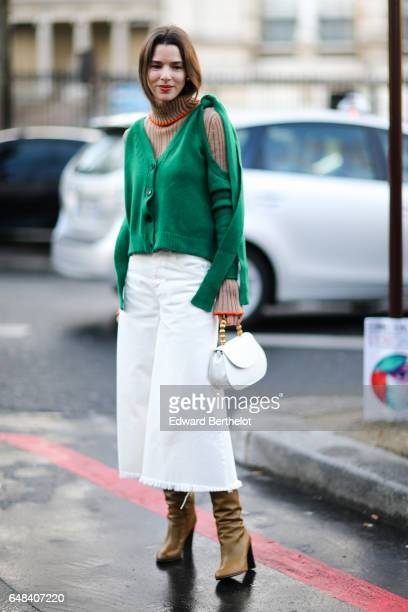 A guest wears a green top a white bag a white skirt and brown suede boots outside the Mashama show during Paris Fashion Week Womenswear Fall/Winter...