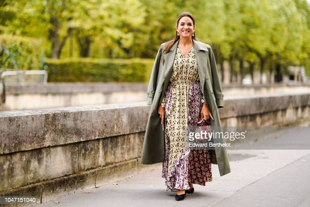 Guest wears a green trench coat, a floral print dress, outside Valentino, during Paris Fashion Week Womenswear Spring/Summer 2019, on September 30,...