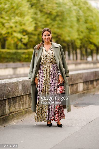 A guest wears a green trench coat a floral print dress outside Valentino during Paris Fashion Week Womenswear Spring/Summer 2019 on September 30 2018...