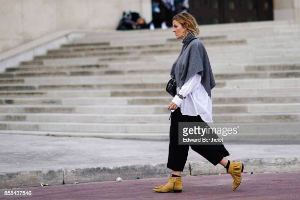 A guest wears a green turtleneck pull over a white shirt black flare pants brown shoes outside Hermes during Paris Fashion Week Womenswear...