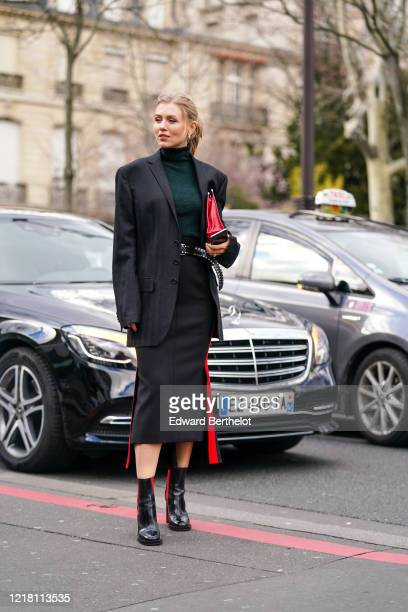 Guest wears a green turtleneck pullover, a black oversized blazer jacket, a belt, a black skirt, black and red shiny boots, a red leather bag,...