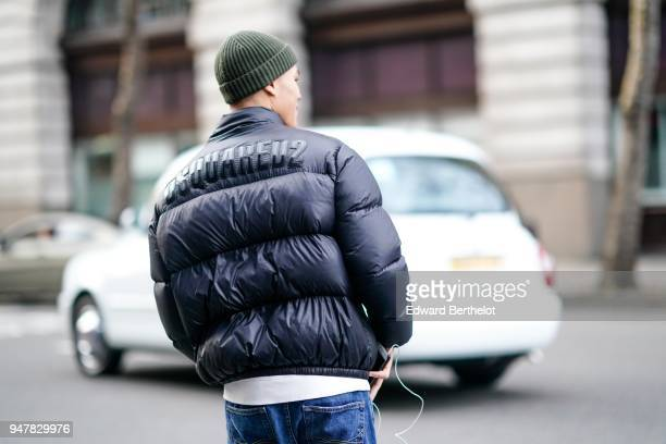 A guest wears a green wool beanie hat a black puffer jacket during London Fashion Week Men's January 2018 at on January 6 2018 in London England