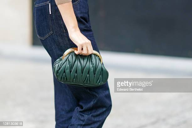 A guest wears a green woven leather Miu Miu bag blue hem jeans outside Miu Miu during Paris Fashion Week Womenswear Spring Summer 2021 on October 06...