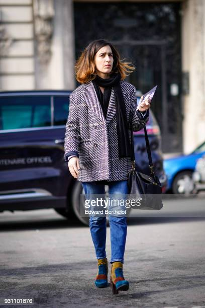 A guest wears a grey and white tweed short coat a black scarf blue jeans a black bag and a pair of yellow blue and brown suede boots during Paris...