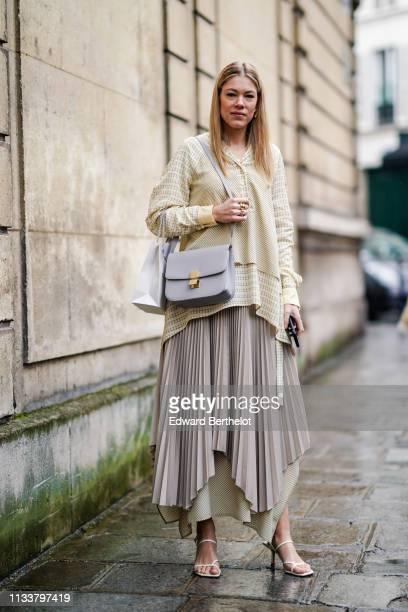 A guest wears a grey bag a pale green asymmetric top a beige asymmetric pleated skirt white sandals outside Nobi Talai during Paris Fashion Week...