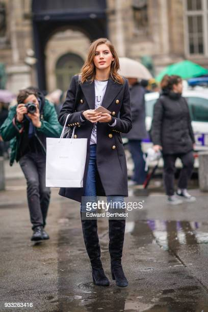 A guest wears a grey brass buttons blue skinny jeans black kneehigh boots outside Balmain during Paris Fashion Week Womenswear Fall/Winter 2018/2019...