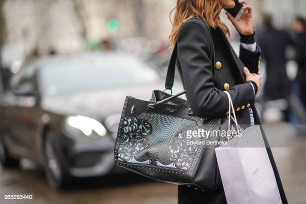 A guest wears a grey brass buttons coat a black embossed leather shopping bag outside Balmain during Paris Fashion Week Womenswear Fall/Winter...
