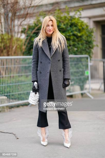 A guest wears a grey doublebreasted coat a black top black crop flare pants black gloves a white flounced hanbag offwhite pointy toe pumps with...