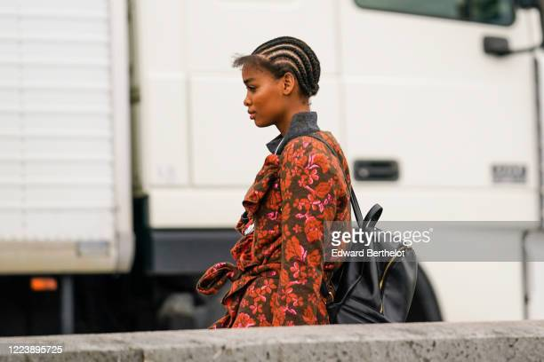 Guest wears a grey hi-neck sweater, a red floral print frilly coat, a black backpack, outside Paco Rabanne, during Paris Fashion Week - Womenswear...