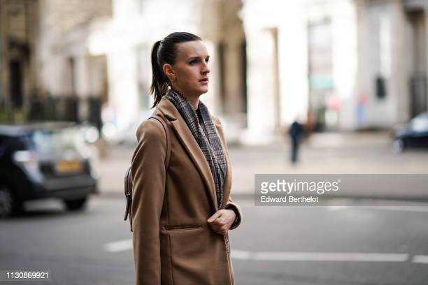 A guest wears a grey Prince of Wales check scarf a camel coat during London Fashion Week February 2019 on February 19 2019 in London England