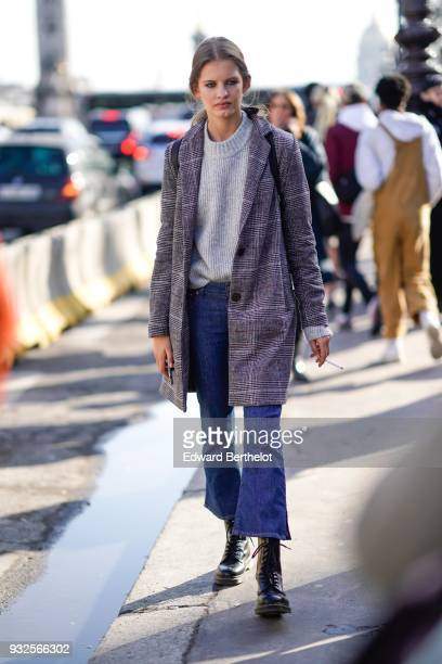 A guest wears a grey princeofwales checkered coat an offwhite sweater blue crop flare jeans black laceup booties during Paris Fashion Week Womenswear...