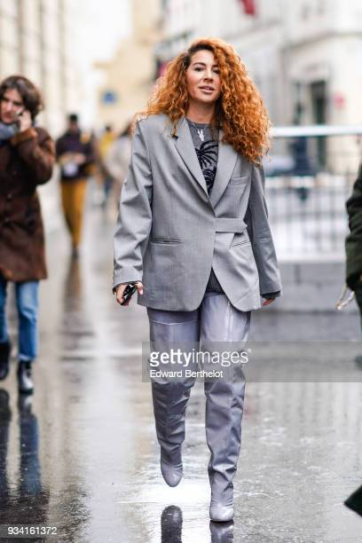 A guest wears a grey sweater with black palm print a light grey jacket light grey glossy vinyl thighhigh boots during Paris Fashion Week Womenswear...