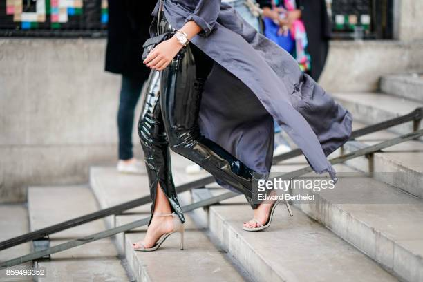 A guest wears a grey trench coatblack vinyl zipped pants outside the Rochas show during Paris Fashion Week Womenswear Spring/Summer 2018 on September...