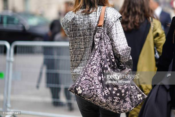 A guest wears a grey tweed pattern jacket a large black Chanel soft bag with white printings of Chanel symbols outside the Chanel Cruise Collection...