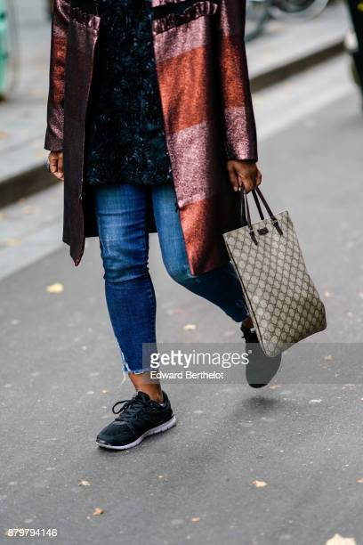A guest wears a Gucci bag cropped denim blue jeans black sneakers outside Koche during Paris Fashion Week Womenswear Spring/Summer 2018 on September...