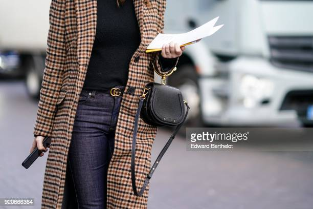 A guest wears a Gucci belt and a Chloe bag during London Fashion Week February 2018 on February 18 2018 in London England