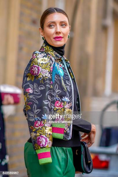 A guest wears a Gucci bomber jacket with embroidered flowers green leather pants outside Simone Rocha during London Fashion Week September 2017 on...