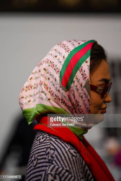 A guest wears a Gucci green and red and pink floral print scarf sunglasses during London Fashion Week September 2019 on September 13 2019 in London...