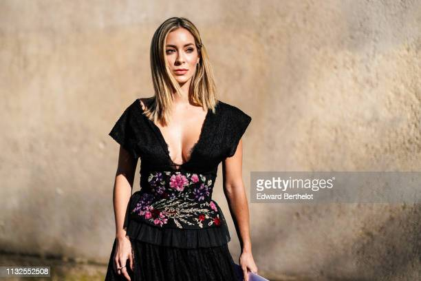 A guest wears a hair clip earrings a lowcut black lace ruffled dress with colorful floral embroideries on the waist outside Dior during Paris Fashion...