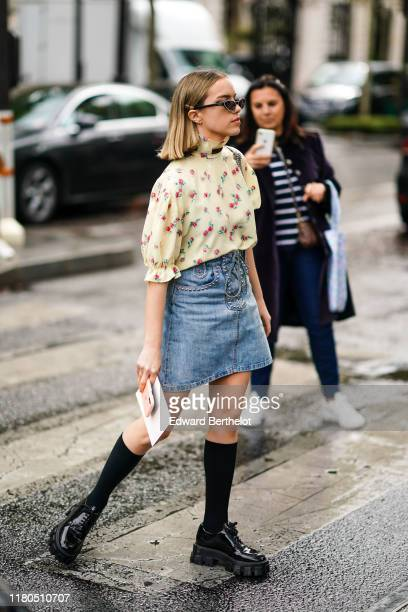 Guest wears a hairpin, earrings, Miu Miu sunglasses, a floral print cream-color puff sleeves top with a hi-neck and a brown lavaliere, a blue denim...