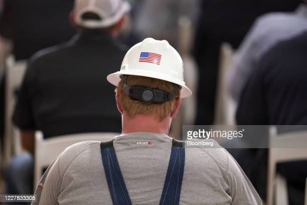 A guest wears a hard hat displaying an American flag while waiting for US President Donald Trump to deliver remarks at a Double Eagle Energy Holdings...