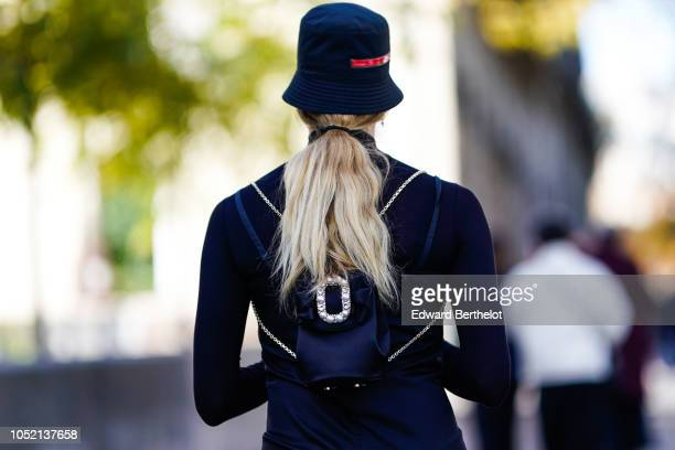 A guest wears a hat a backpack outside Haider Ackermann during Paris Fashion Week Womenswear Spring/Summer 2019 on September 29 2018 in Paris France
