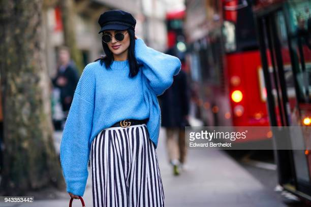 A guest wears a hat a blue oversize pull over a Gucci belt a black and white striped skirt during London Fashion Week February 2018 on February 16...