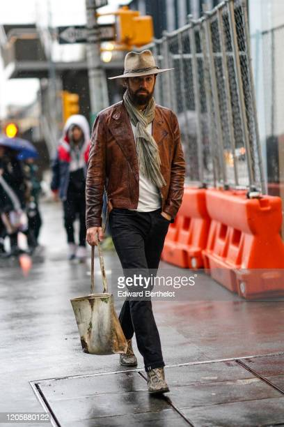 Guest wears a hat, a brown leather jacket, a scarf, black denim pants, snake print boots, a bag, during New York Fashion Week Fall Winter 2020, on...