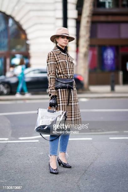 A guest wears a hat a brown plaid checked trench coat a black studded bag a plastic bag studded black leather gloves ripped jeans studded shoes...