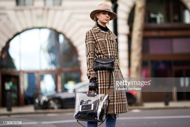 A guest wears a hat a brown plaid checked trench coat a black studded bag a plastic bag studded black leather gloves ripped jeans earrings during...