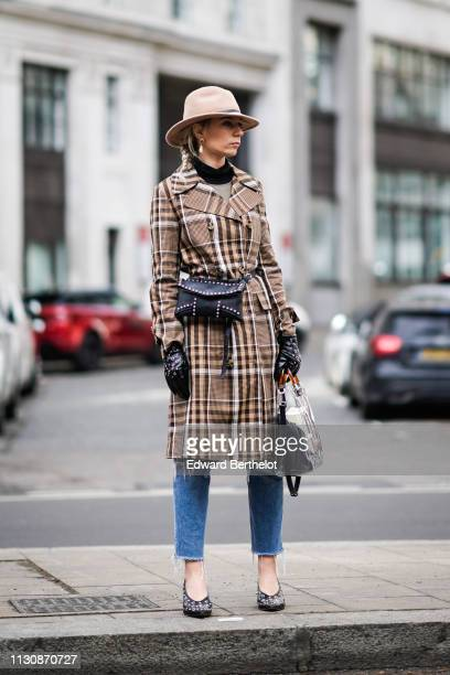 A guest wears a hat a brown plaid checked trench coat a black studded bag a plastic bag studded black leather gloves ripped jeans earrings studded...