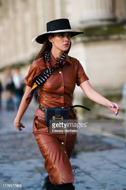 A guest wears a hat a colored scarf a brown leather dress a Prada belt bag with a golden chain fluffy black pants outside Louis Vuitton during Paris...