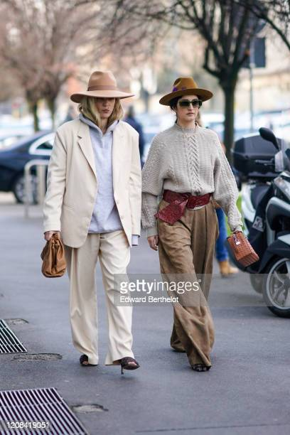 Guest wears a hat, a hoodie sweater, a white oversized blazer jacket, a brown puff leather bag, white pants, shoes ; a guest wears a hat, sunglasses,...