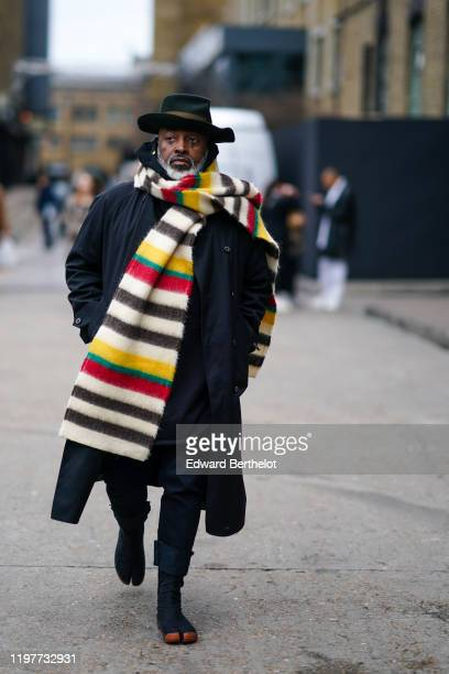 A guest wears a hat a long and oversized colored striped wool scarf a black long coat shoes with apparent toes during London Fashion Week Men's...