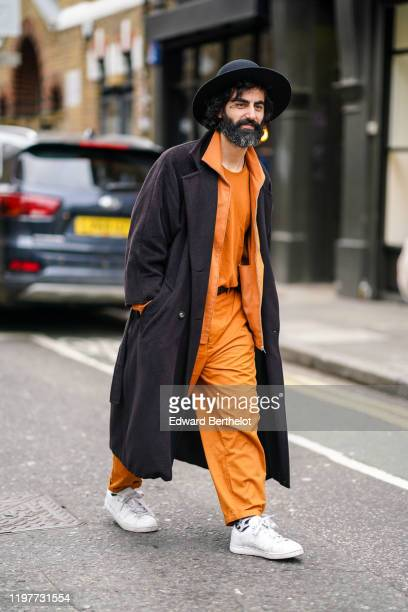A guest wears a hat a long coat an orange jacket an orange tshirt orange pants white sneakers shoes during London Fashion Week Men's January 2020 on...