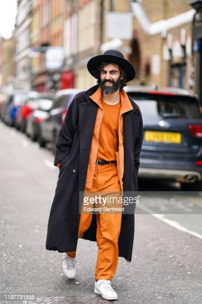 Guest wears a hat, a long coat, an orange jacket, an orange t-shirt, orange pants, white sneakers shoes, during London Fashion Week Men's January...