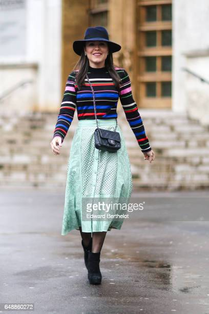 A guest wears a hat a multicolor striped pull over a green lace skirt a Chanel bag and black shoes outside the Valentin Yudashkin show during Paris...