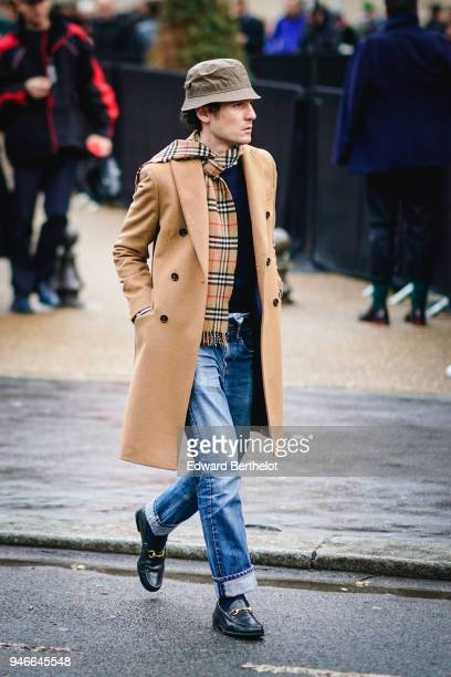 A guest wears a hat a tartan scarf a brown coat blue jeans black shoes outside Dior during Paris Fashion Week Menswear Fall Winter 20182019 on...