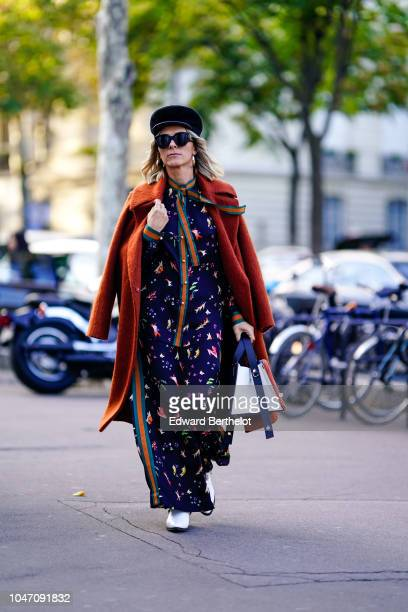 A guest wears a hat sunglasses an orange coat white shoes a multicolor print outfit outside Shiatzy Chen during Paris Fashion Week Womenswear...