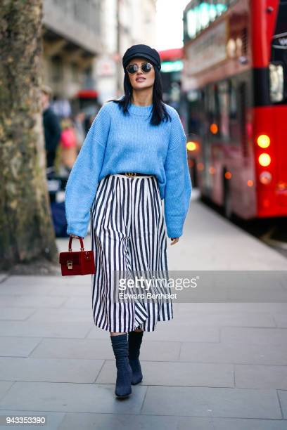 A guest wears a hat sunglasses blue oversized pull over a black and white striped skirt a red bag shoes during London Fashion Week February 2018 on...