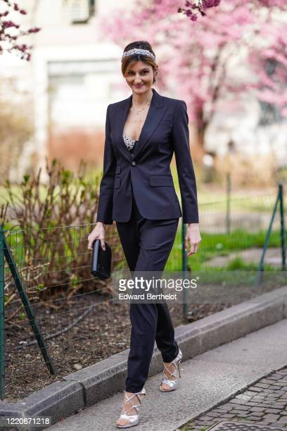 Guest wears a headband, a black jacket, bras, black pants, silver shoes, a clutch, outside Koche x Pucci, during Milan Fashion Week Fall/Winter...