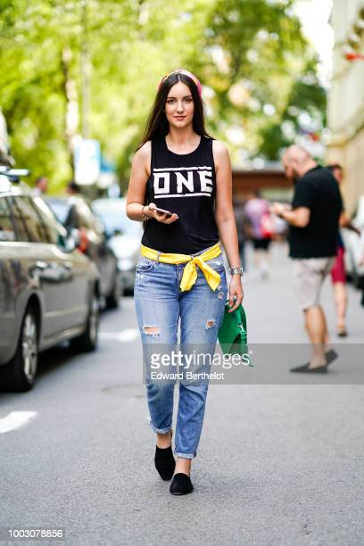 A guest wears a headband a black tank top a white belt ripped jeans black shoes during Feeric Fashion Week 2018 on July 21 2018 in Sibiu Romania