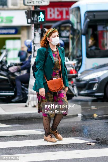 A guest wears a headband a green oversized blazer jacket a khaki and pink floral print dress an orange bag black tights with polka dots beige shoes...