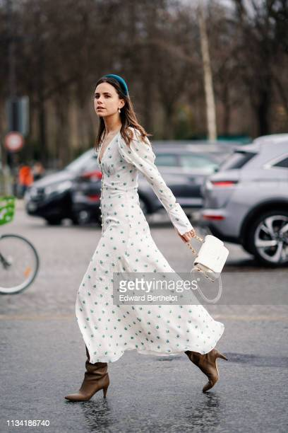 A guest wears a headband a white dress with printed blue flowers a white Chanel bag outside Chanel during Paris Fashion Week Womenswear Fall/Winter...