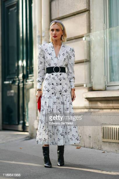 Guest wears a headband, a white dress with printed shapes, a red bag, black leather pointy shoes, a belt, outside Alessandra Rich, during Paris...