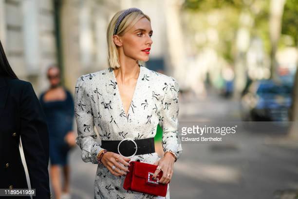 Guest wears a headband, a white dress with printed shapes, a red bag, outside Alessandra Rich, during Paris Fashion Week - Womenswear Spring Summer...