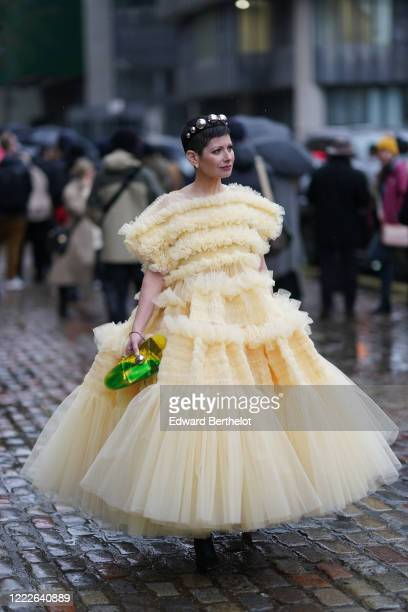 Guest wears a headband with metallic silver spheres, earrings, a pale pastel yellow ruffled pleated dress during London Fashion Week Fall Winter...