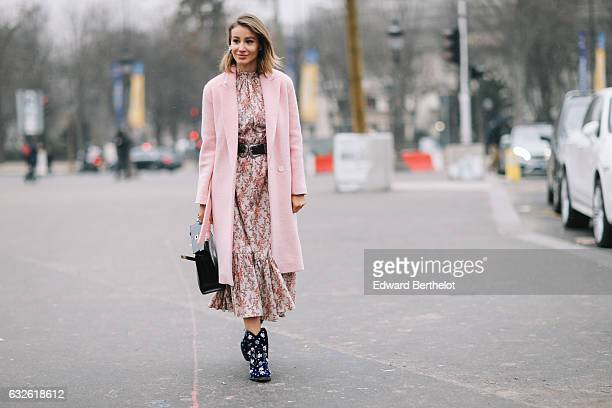 A guest wears a Hermes black bag a pink coat a floral print dress and shoes with colored prints outside the Chanel show at the Grand Palais during...